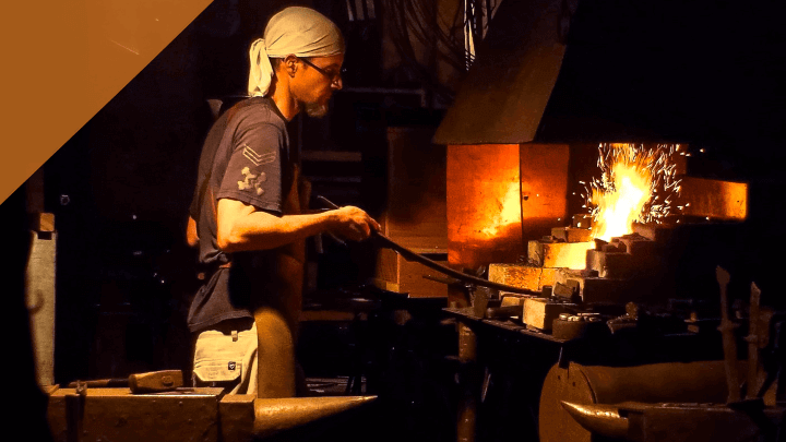 a blacksmith fueling a fire