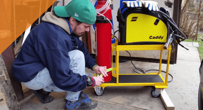 a professional welder setting up his equipment on a cart